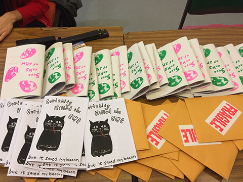 "table of zines, one is ""Curiosity Kill the Cat,"" another is ""Fragile,"" the 3rd is upside down"